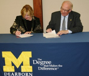 HFCC President Gail Mee and UM-Dearborn Chancellor Daniel Little sign a reverse transfer agreement