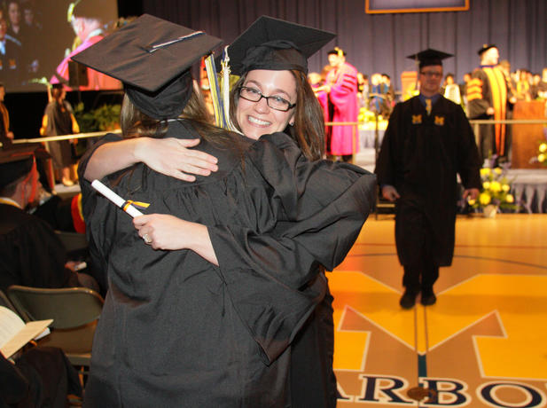 New graduates hugging at UM-Dearborn's commencement.