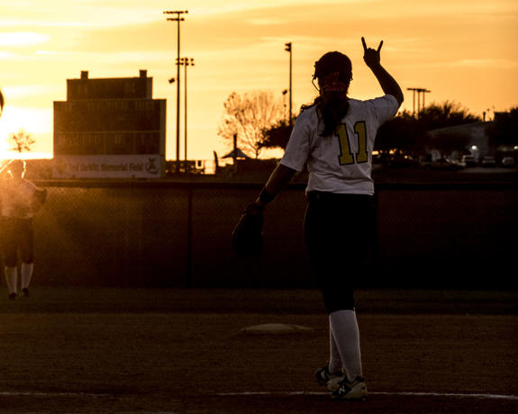 Silhouette of a UM-Dearborn softball player at twilight.
