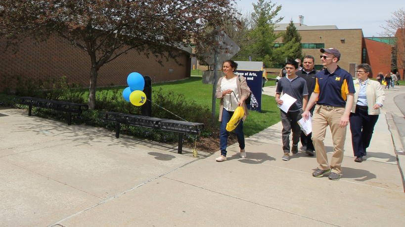 Group of prospective students and families walking on campus.