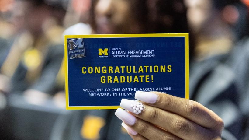 A woman holds a card that reads, Congratulations, Graduate!