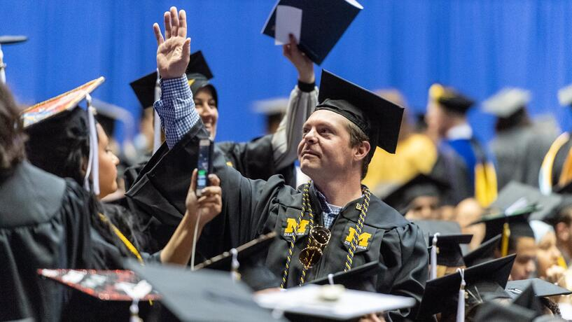 A man looks up and raises his hand at commencement