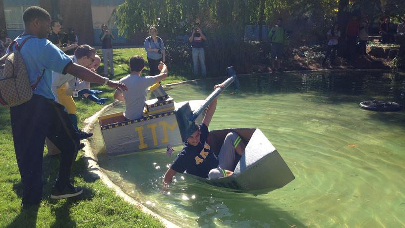 ITM Club and Alpha Kappa Psi members competing in the annual Cardboard Boat Race during Homecoming Week.