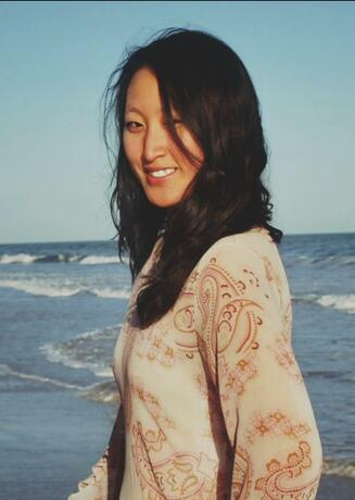 Sara stands on a beach looking to her left towards the camera as the wind blows her hair