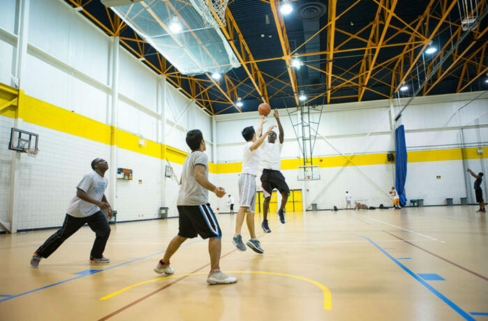 Students playing basketball in the university fieldhouse
