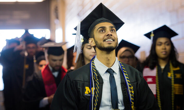 A student in a cap and gown walking into commencement