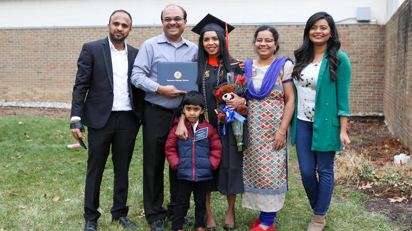 A graduate student with her family and friends at a commencement cermony