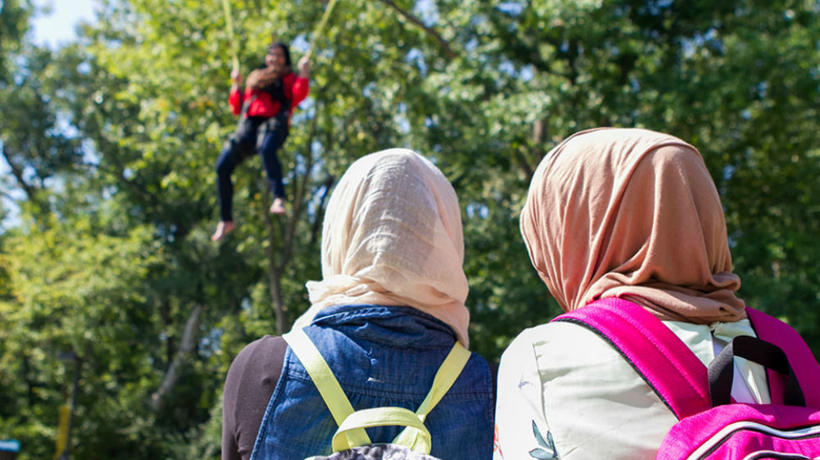 Two students look on as one student jumps over a trampoline