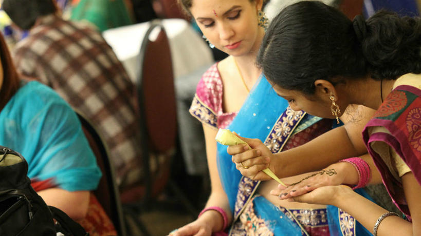 Student applying henna on another student during Global Fest