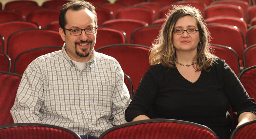 Paula and Tim Guthat, '93 B.A., sit in the seats of the theater.