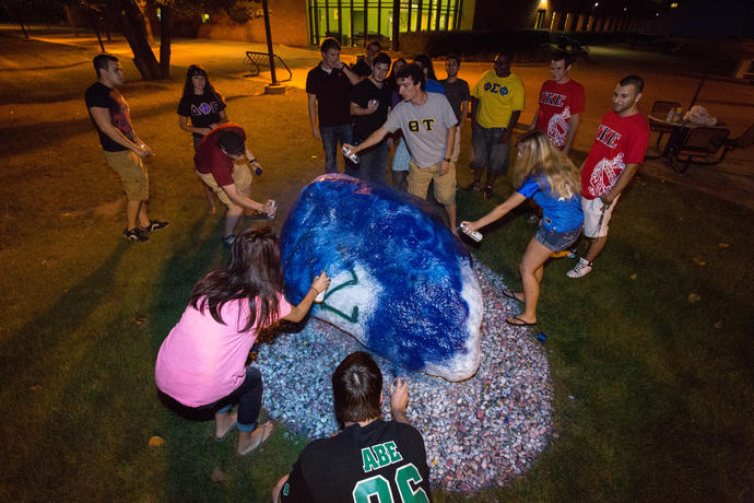 Fraternity and sorority members painting the campus rock together.