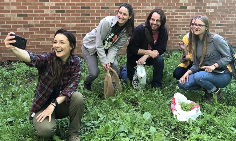 Field biology students forage in grass for course assignment