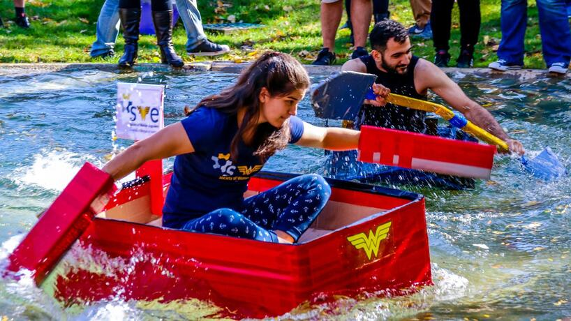 Students compete in the Cardboard Boat Races on Chancellor's Pond during Homecoming.