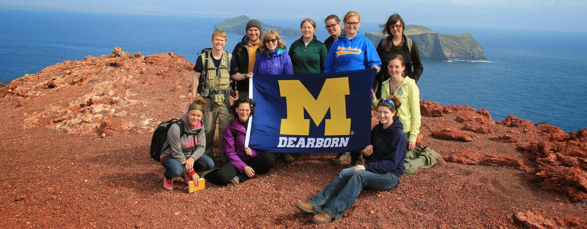 Students in Iceland holding a UM-Dearborn flag.