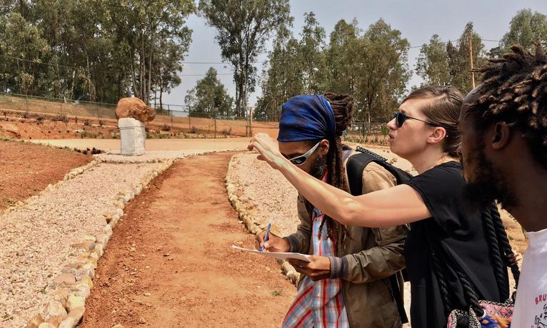CASL faculty members traveled to Rwanda this summer. Anna Muller speaks to landscapers in the Garden of Memory.