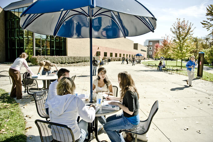Students at the picnic tables outside the UC.