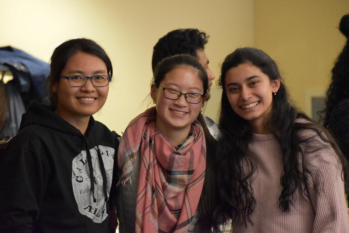 Three international students smiling at the graduate international student reception