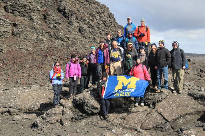 Students holding a UM-Dearborn flag in front of rock formation while on study abroad in Iceland