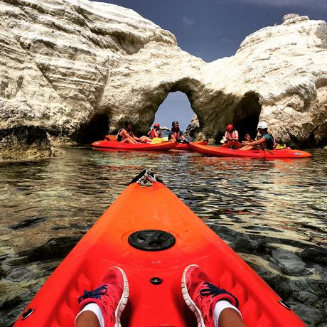 People kayaking in front of large rock formations in Croatia