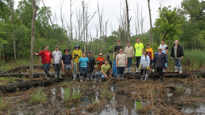 Boy Scout Kyle Polidori plants native species in marsh in Environmental Study Area