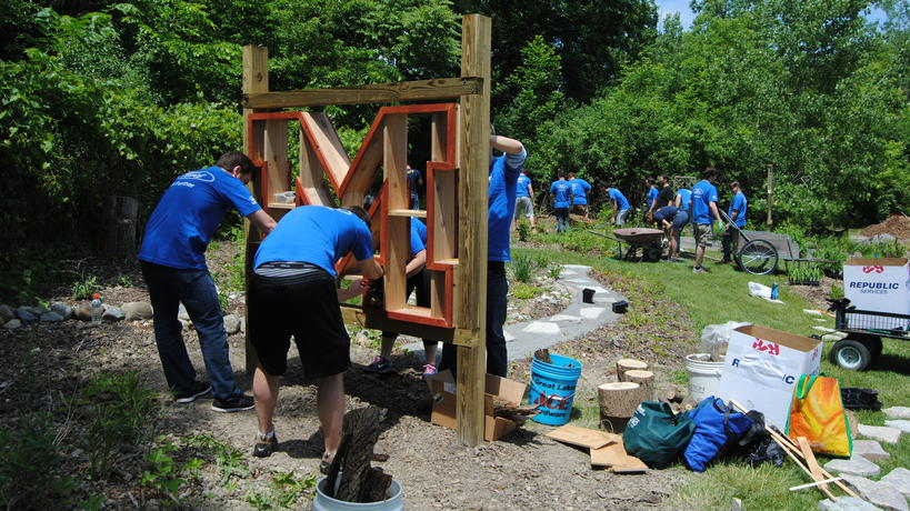 Ford volunteers working on the Go Blue! Insect Hotel in the Pollinator Garden