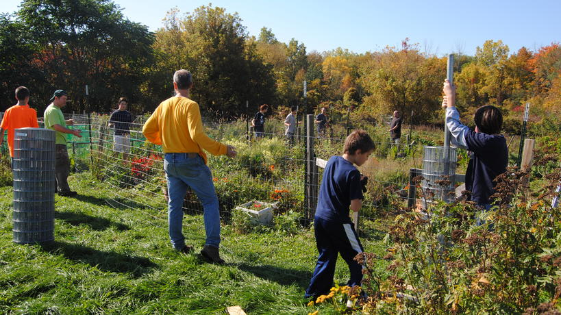 Volunteers install fencing in Children's Garden of Community Organic Garden