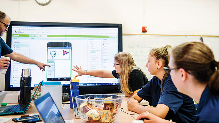 Coding instructor Josh Rychlicki (left) and UM-Dearborn student Jessica Sterly (center) help camp participants review the visual interface design they came up with for a golf app.