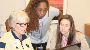 Associate Professor Karen Thomas-Brown, center, talks with teacher Elise Bommarito, right, on ways to use new technology.