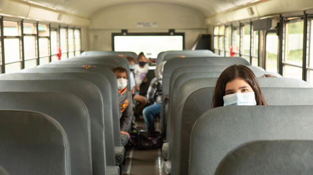 Masked elementary students on a half-full school bus.