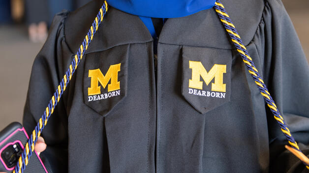 Photo of UM-Dearborn wearing their graduation robe and cords