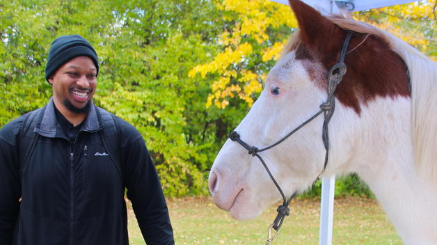 Sophomore Frank Carter, an Army veteran, with horse Top Secret during Veterans Week