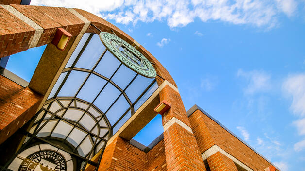 An artistic shot of the university seal on the Social Sciences Building set against a blue sky