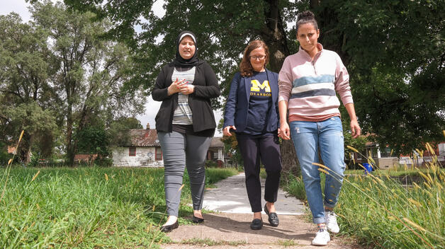 In Detroit's Delray neighborhood, Assistant Professor OF Public Health Natalie Sampson (center) walks with senior Valeria Cossyleon (right) and Janine Hussein ('18), two UM-Dearborn students who helped collect door-to-door health surveys.