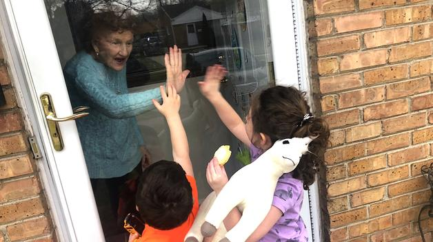 A great-grandmother is greeted by young family members at a socially safe distance during the Coronavirus pandemic.