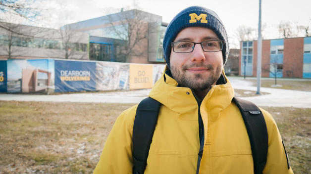 Mechanical engineering doctoral student Ruslan Akhmedagaev in his maize and blue winter gear outside the new Engineering Lab Building.