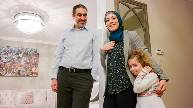 UM-Dearborn graduate Ahmad Nasser standing and smiling with his wife and daughter in their home in Livonia.