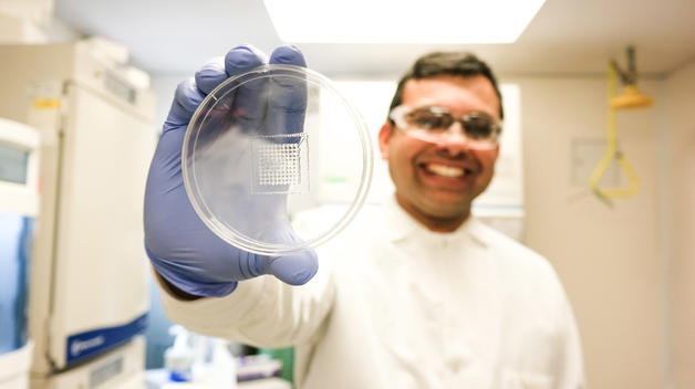 Wearing a white lab coat, mechanical engineering professor Nilay Chakraborty holds up a Petri dish containing 3D printed cells.