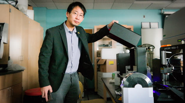 Bioengineering professor Joe Lo stands next to a 3D printer in his lab