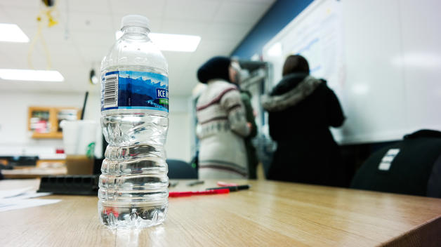 Bottled water sitting on a desk with students in the background writing on a whiteboard.