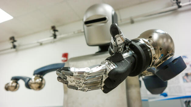 A black and silver humanoid robot extending its arm in a research lab on the UM-Dearborn campus.