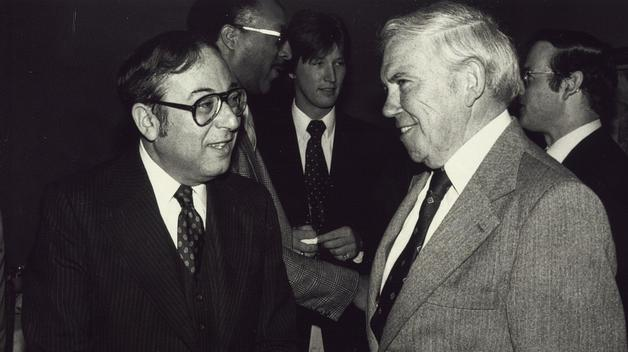 Acting Chancellor Bernie Klein talks to UAW President Doug Fraser following Spring 1980's Commencement ceremony.
