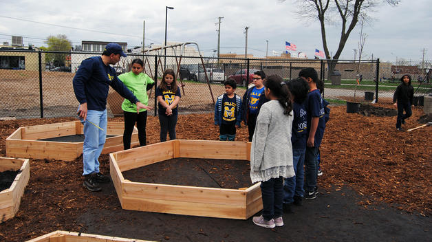 Dr Susko gives children instructions during the installation of a garden at Miller Elementary School
